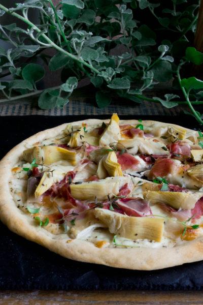 Pizza z białym sosem, karczochami, szynką i parmezanem